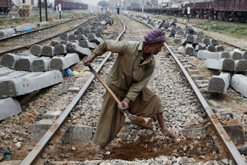 A laborer uses a shovel to dig the ground before replacing concrete sleepers along railway tracks in Karachi