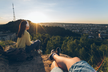 couple sitting  on the peak of the hill and looking on sunset