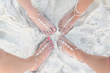 Bride and Bridesmaids Feet With Jeweley in the sand on the beach