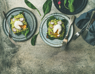 Healthy vegetarian breakfast flat-lay. Whole-grain toasts with avocado, spinach and poached eggs over grey concrete background, top view, copy space. Clean eating, gluten-free, diet food concept