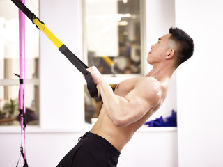 asian body builder exercising in gym using fitness straps