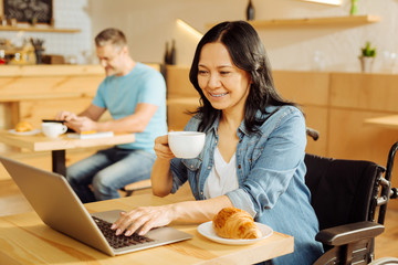 Cafe. Beautiful cheerful dark-haired crippled woman sitting in a wheelchair and holding a cup of coffee and working on her laptop and a man sitting in the background