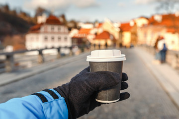 The hand holds a hot drink in a takeaway mug against the background of the old European city, the concept of weekend travel