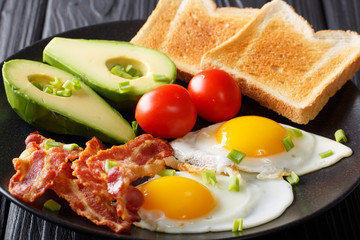 hearty breakfast: fried eggs with bacon, avocado, toast and tomatoes close-up on a plate. horizontal
