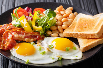 Delicious fried eggs, bacon, beans, toast and fresh vegetable salad on a plate. horizontal