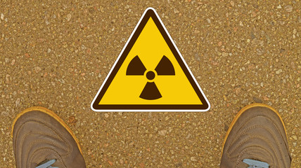 Shoes on a background of asphalt and sign the radiation safety.