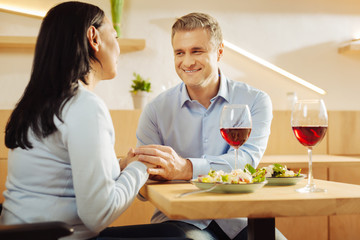 Red wine. Content disabled dark-haired woman and a handsome smiling well-built man sitting in a cafe and holding hands and having romantic dinner