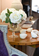 wooden table and cozy purple armchair with white roses and white ceramic birds as decoration