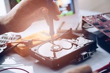 Technician repairing broken hard disk drive