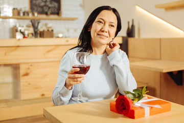 Resting. Beautiful content dark-haired woman smiling and drinking wine and a present a rose lying on the table
