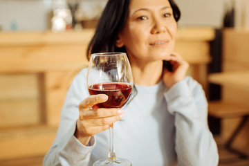 Thinking. Attractive thoughtful dark-eyed woman thinking and looking in the distance while drinking red wine
