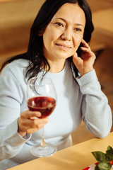 Relaxation. Beautiful content dark-eyed woman smiling and looking in the distance while drinking red wine