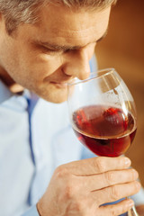 Wine. Attractive serious blond man drinking wine and wearing a blue shirt while relaxing