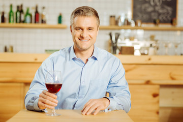 Recreational. Handsome exuberant well-built man drinking wine and wearing a blue shirt while relaxing