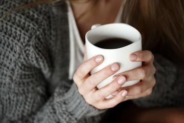 Human hand holding coffee mug