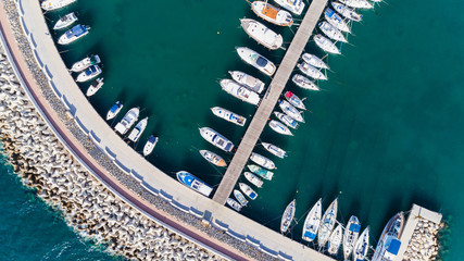 Aerial bird's eye view of Zygi fishing village port, Larnaca, Cyprus. Bird eye view of aligned fish boats moored in the harbour, docked yachts, pier, wave breaker rocks near Limassol city from above.