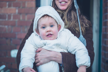 Mother with warmly dressed baby outside