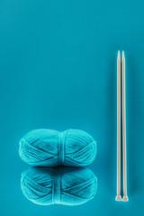 blue knitting yarn balls with knitting needles, isolated on blue