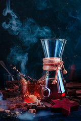 Glass coffee cup with a dynamic splash and rising steam. Hourglass-shaped coffeemaker with on a dark background with copy space. Action food photography. Alternative coffee brewing concept.