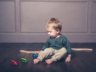 Cute little boy playing with wooden train