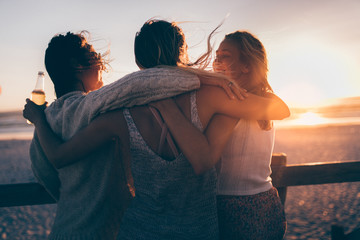 Groupf of female friends hugging each other in sunset