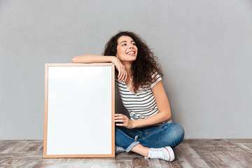 Caucasian woman with beautiful hair posing with legs crossed demonstrating big great painting or portrait isolated over grey wall copy space
