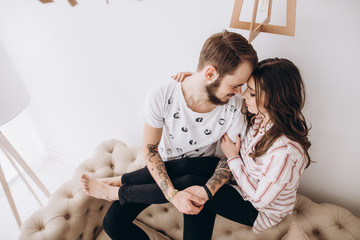 Young spouses spend time together in their cozy bedroom. Love story, happy family, side view