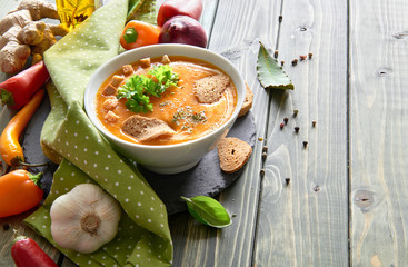 Spicy vegetable soup with baked bell peppers on wood, text space
