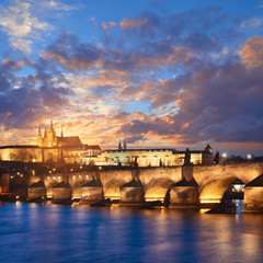 Oświetlony Most Karola znajduje odzwierciedlenie w Wełtawie wczesnym wieczorem