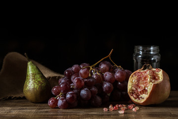 Pictorial still life with grapes, pears and pomegranate.