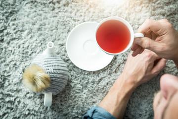 Mann relaxt mit tee zu hause