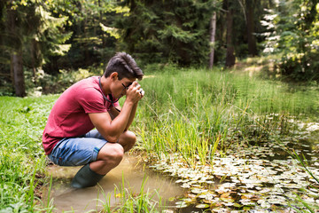 Teenage boy with camera in the lake, taking picture.
