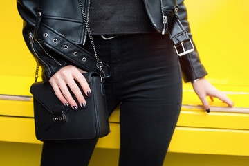 Outdoor fashion details.close up fashion details. perfect spring outfit acessories. young fashion blogger holding her trendy brown handbag. perfect elegant purse.Yellow urban background