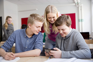 Teenagers looking at cell phone in classroom