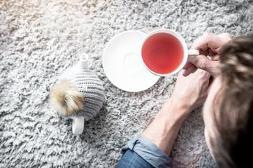 erholung mann mit tee relaxt auf dem fußboden