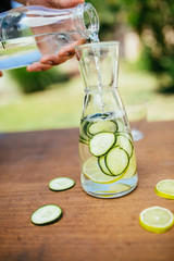 Pouring Water In The Bottle With Cucumber