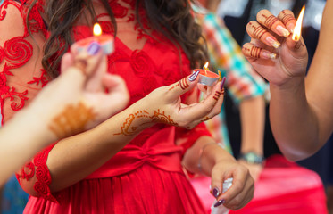 The bride decorated with a decorative candlestick in her hands and a sign . holds a candle in her hand . in the background without focus . The bride has a candle in his hand . Candles burn