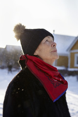 Senior woman standing in front of house in winter