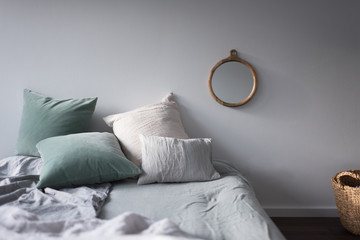 Bett mit Kissen und Spiegel in Pastelltönen im Sonnenschein