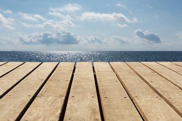 leere Holzbretter mit Meer und blauem Himmel im Hintergrund