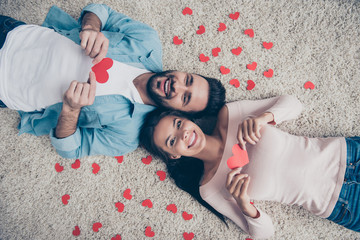 I'll give you my heart! Man decided to show his feelings!  Top view photo of excited cheerful lovely cute beautiful lovers holding heart cards in hands, lying on the floor