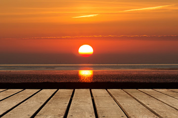 leere Holzboden Bretter vor einer aufgehenden Sonne über dem Meer