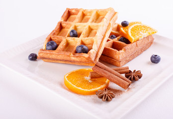 Traditional Belgian waffles with blueberries, banana andand cinnamon on a white plate. Gourmet Breakfast. Close up