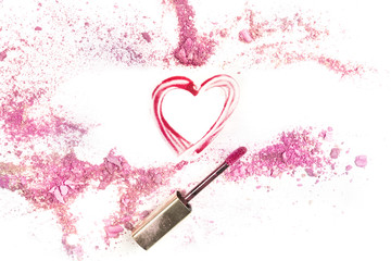 Heart drawn with lip gloss on white background with eye shadow