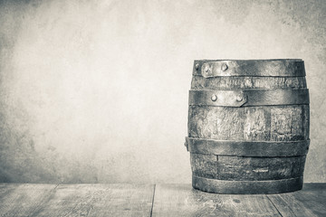 Classic old retro aged oak barrel with hoops on wooden floor front concrete wall background. Vintage style sepia photo