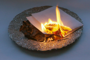 Document burning in vintage plate. Paper sheet with text burning in fire.
