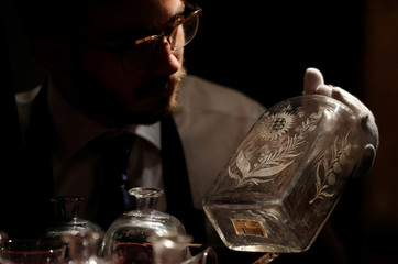 """A member of Sotheby's staff poses for a photograph with a decanter from the """"Grog Chest"""" which forms part of a sale of items called Nelson's Legend, in London"""