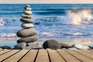 Holzboden leer mit gestapelten Steinen am Strand
