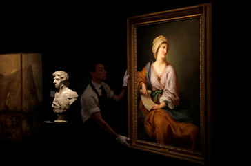 A member of Sotheby's staff poses for a photograph with a  portrait of Emma Hamilton which forms part of the sale of items celebrating Nelson's Legend, in London
