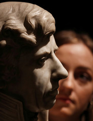 A member of Sotheby's staff poses for a photograph with a marble bust of Lord Nelson union which forms part of a sale of items called Nelson's Legend, in London